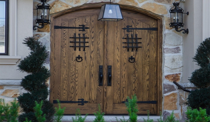 Beautiful Red Oak double door with a curve on top and decorative wrought iron by Master Doors, Toronto
